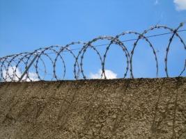 Gefängniszaun an grauer Mauer