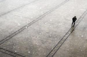 Ein Mensch ganz alleine auf nasser Strasse