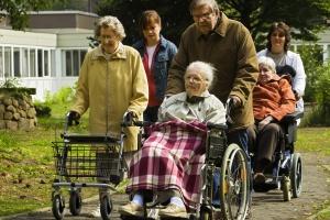 Alte Menschen, zum Teil im Rollstuhl, auf dem Weg durch einen Park