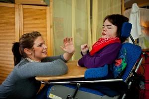 Junge Frau kniet vor einer anderen jungen Frau im Rollstuhl und reicht ihr die Hand