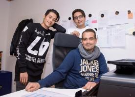 Zwei junge Flüchtlinge stehen im Büro hinter Sozialarbeiter Oliver Nickel