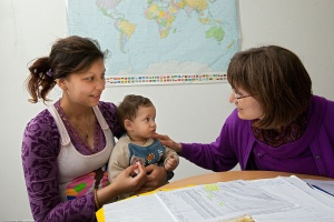 Eine Frau mit Kind auf dem Schoß sitzt in der Beratung