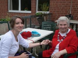 Kati Lovas sitzt am Tisch mit Sieglinde und drückt ihre Hand
