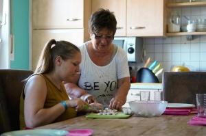 Mädchen schneidet mit Frau Gemüse in einer Küche