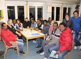 Flüchtlinge sitzen mit Ehrenamtlichen um einen Tisch im Café International
