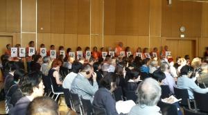 Konferenzsaal mit Menschen, die Buchstaben hochhalten