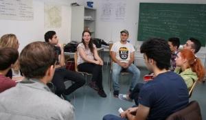 Integrationskursteilnehmer sitzen im Kreis vor einer Tafel