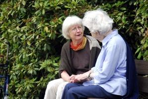 Zwei ältere Frauen sitzen einander zugewandt auf einer Bank im Grünen