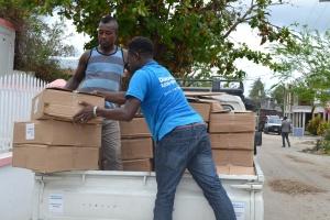 Zwei dunkelhäutige Männer laden Pakete von einem offenen Lieferwagen