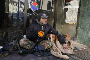 Bettler mit Hund sitzt in einem Geschäftseingang