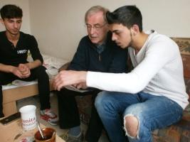 Älterer Mann sitzt mit zwei Jugendlichen auf dem Sofa und schaut sich Papiere an