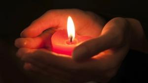 Hand hält brennende Kerze im Dunkeln