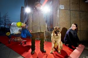 Mann mit grauem Bart, Schäferhund stehen auf einem roten Teppich, eine junge Frau, die den Teppich weiter ausrollt