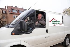 Älterer Mann schaut aus Fenster eines weißen Lieferwagens