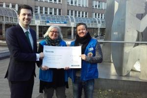 Ein Bankmitarbeiter übergibt zwei Mitarbeiterinnen in blauen Westen der Bahnhofsmission einen großen Scheck