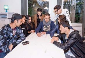Jugendliche Flüchtlinge sitzen um einen Tisch mit einem Betreuer