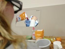 Frau sitzt mit Datenbrille vor Backutensilien