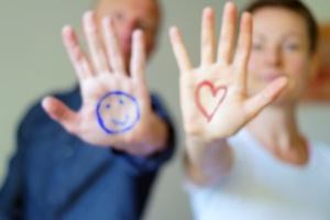 zwei Hände abwehrend, mit einem lachenden Gesicht und einem Herz auf die Hände gemalt