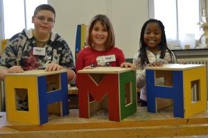 Drei Kinder zeigen selbstgebaute, bunte Hocker