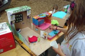 Ein Mädchen sitzt vor selbst gebasteltem Puppenhaus