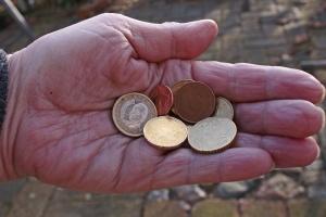 Ältere Hand mit Münzen