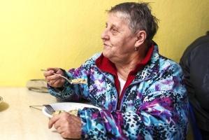 Alte Frau in billiger Kleidung beim Essen einer Suppe