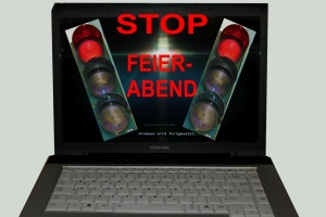 """Aufgeklappter Laptop mit Ampel und Aufschrift """"Stop! Feierabend"""""""