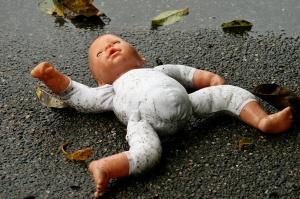 Nackte Puppe liegt auf dunklem Asphalt