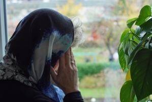 Frau mit Kopftuch blickt aus dem Fenster