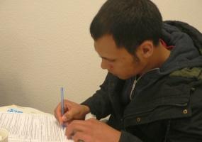 Junger Flüchtling unterschreibt Formular