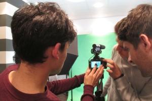 Drei Jugendliche stehen um eine Kamera herum