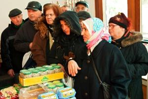 Menschen warten gedrängt in einer Schlange vor der Ausgabe von Dosen und Eiern