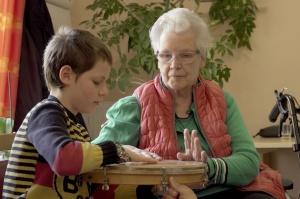 Eine alte Frau und ein Junge schlagen gemeinsam eine Handtrommel