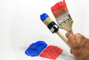 Eine Hand hält zwei Farbpinsel hoch
