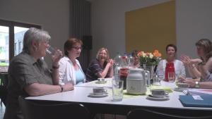 Frauen sitzen um einen Tisch und reden