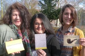 Drei Frauen halten Postkarten hoch