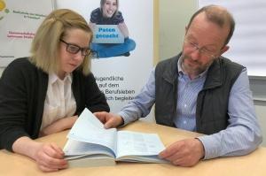 Mädchen und älterer Mann schauen in ein Buch