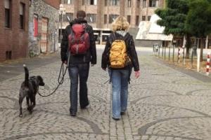 Mann und Frau von hinten, mit Rucksack auf dem Rücken und Hund an der Leine