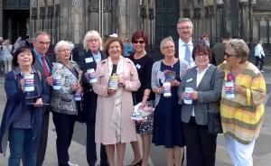 Eine Gruppe von Frauen und ein Mann stehen mit Spendendosen vor dem Kölner Dom