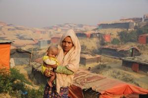 Eine Frau mit Baby steht vor einer Hütte