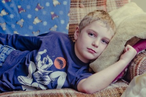 Kind liegt traurig auf einer alten Couch