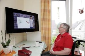Frau im Rollstuhl schaut auf großen Bildschirm