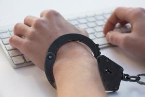 Hand auf Tastatur mit Handschelle