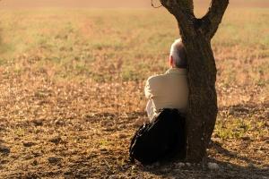Ein älterer Mann sitzt alleine an einem Baum