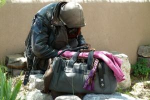 Obdachloser sitzt an einer Mauer