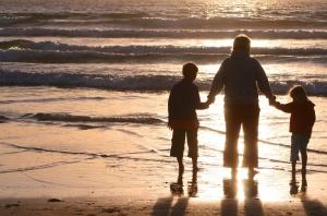 Mann mit Kindern am Strand