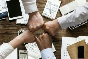 Hände symbolisieren Zusammenhalt im Büro