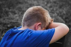 Ein Junge lehnt traurig an einer Mauer