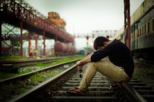 Verzweifelter Mann sitzt auf Bahngleisen