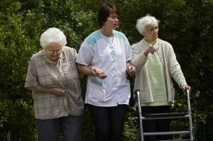 Pflegerin mit zwei alten Menschen
